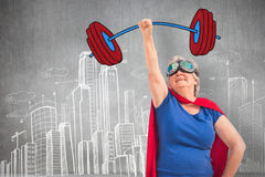 Composite image of senior woman disguise as superhero with hand raised Royalty Free Stock Images