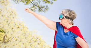 Composite image of senior woman wearing superwoman costume Royalty Free Stock Photo