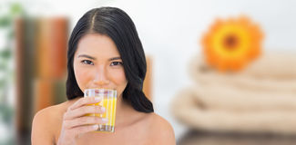 Composite image of sensual nude model drinking orange juice Royalty Free Stock Photography