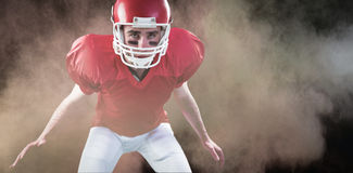 Composite image of a serious american football player taking his helmet looking at camera Stock Photography
