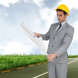 Composite image of serious architect with hard hat looking at plans Stock Photography