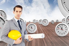 Composite image of serious architect holding plans and hard hat Royalty Free Stock Images
