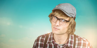 Composite image of serious blond hipster staring. Serious blond hipster staring against blue green background Royalty Free Stock Photos
