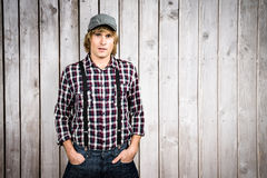 Composite image of serious blond hipster staring at camera. Serious blond hipster staring at camera against wooden planks Stock Image