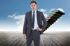 Composite image of serious businessman with hand on hip Royalty Free Stock Photo
