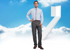 Composite image of serious businessman with hand on hip Stock Photography