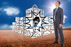 Composite image of serious businessman with hand in pocket Royalty Free Stock Images