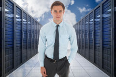 Composite image of serious businessman with hand in pocket Stock Photo