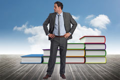 Composite image of serious businessman with hands on hips. Serious businessman with hands on hips against book steps against sky Royalty Free Stock Image