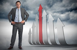 Composite image of serious businessman with hands on hips Stock Image