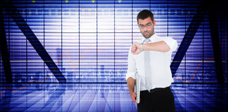 Composite image of serious businessman holding laptop checking time Royalty Free Stock Image