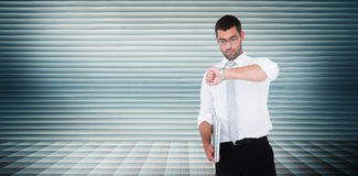 Composite image of serious businessman holding laptop checking time Royalty Free Stock Images