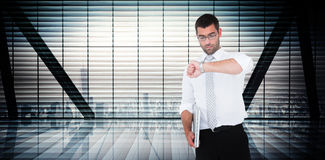 Composite image of serious businessman holding laptop checking time Royalty Free Stock Photography