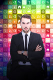 Composite image of serious businessman sitting with arms crossed. Serious businessman sitting with arms crossed against app wall Stock Images