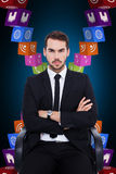 Composite image of serious businessman sitting with arms crossed Stock Photos