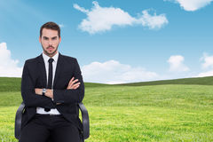 Composite image of serious businessman sitting with arms crossed. Serious businessman sitting with arms crossed against blue sky over green field Royalty Free Stock Image