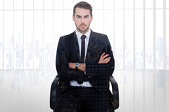 Composite image of serious businessman sitting with arms crossed Royalty Free Stock Photo