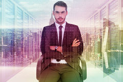 Composite image of serious businessman sitting with arms crossed. Serious businessman sitting with arms crossed against server room with towers Royalty Free Stock Photography