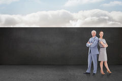 Composite image of serious businessman standing back to back with a woman Royalty Free Stock Photography