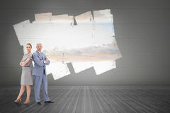 Composite image of serious businessman standing back to back with a woman Stock Photos