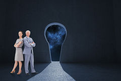 Composite image of serious businessman standing back to back with a woman Royalty Free Stock Photos
