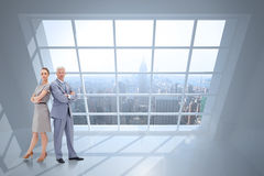 Composite image of serious businessman standing back to back with a woman Stock Image