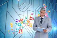 Composite image of serious businessman using tablet pc looking at camera Stock Images
