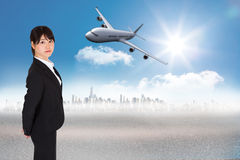 Composite image of serious businesswoman. Serious businesswoman against cityscape on the horizon Stock Photos