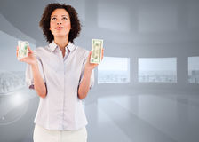 Composite image of serious businesswoman holding dollars and looking upwards Stock Photography