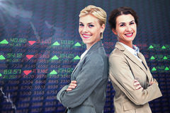 Composite image of serious businesswomen standing back on back Royalty Free Stock Photos