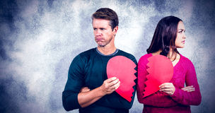 Composite image of serious couple holding cracked heart shape Stock Photos
