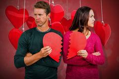 Composite image of serious couple holding cracked heart shape 3D. Serious couple holding cracked heart shape against valentines heart design 3D Royalty Free Stock Photo