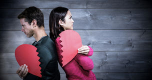 Composite image of serious couple standing back to back Royalty Free Stock Image