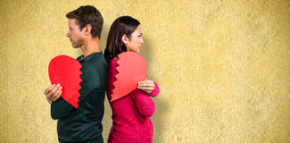 Composite image of serious couple standing back to back Royalty Free Stock Photo