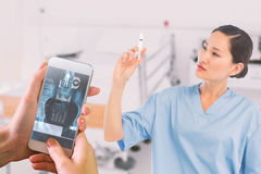 Composite image of serious doctor holding an injection in hospital Stock Images