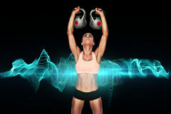 Composite image of serious female crossfitter lifting kettlebells above head. Serious female crossfitter lifting kettlebells above head against blue wave Royalty Free Stock Images