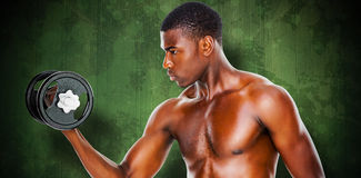 Composite image of serious fit shirtless young man lifting dumbbell Royalty Free Stock Photo