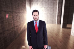Composite image of serious handsome businessman holding briefcase Royalty Free Stock Photography