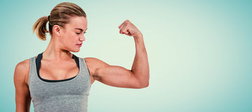 Composite image of serious muscular woman flexing muscle Stock Images