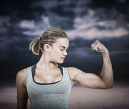 Composite image of serious muscular woman flexing muscle Royalty Free Stock Photography
