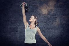 Composite image of serious muscular woman lifting kettlebell Royalty Free Stock Image