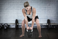 Composite image of serious muscular woman lifting kettlebell Royalty Free Stock Photography