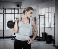 Composite image of serious muscular woman lifting kettlebell Royalty Free Stock Photos