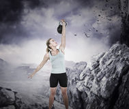 Composite image of serious muscular woman lifting kettlebell Royalty Free Stock Photo
