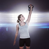 Composite image of serious muscular woman lifting kettlebell Stock Images