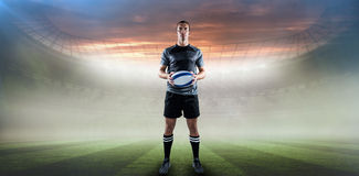 Composite image of serious rugby player in black jersey holding ball Royalty Free Stock Photos