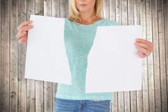 Composite image of serious woman holding torn sheet of paper Royalty Free Stock Photography
