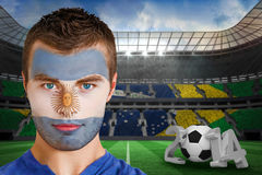 Composite image of serious young argentina fan with face paint Royalty Free Stock Photography