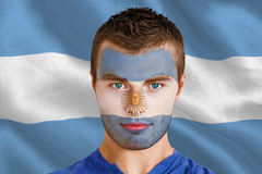Composite image of serious young argentina fan with facepaint Stock Images