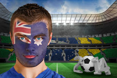 Composite image of serious young australia fan with face paint Royalty Free Stock Photo